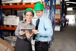 Supervisors Using Digital Tablet At Warehouse Two young supervisors in formalwear using digital tablet at warehouse Graves and Richard, Personal Injury Lawyer Office, St. Catharines, Ontario