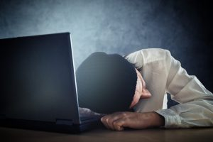 Exhausted man sleeps on laptop at office desk after working overtime.